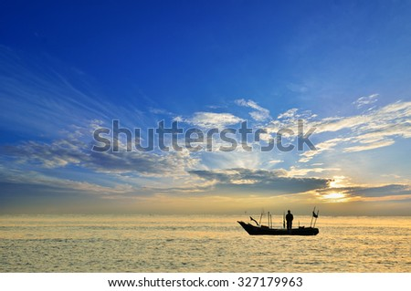 Fishing boat at sunrise (Selective focus. Focus at the boat only) - stock photo