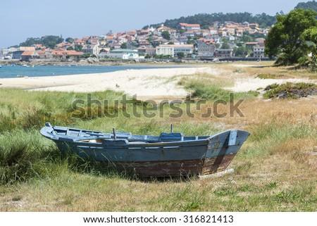 Fishing boat beached on the sand. Photo taken in Aldan, Cangas de Morrazo, Vigo estuary, Pontevedra, Spain - stock photo