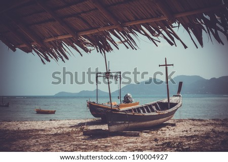 Fishing boat could be seen from a palm roof - stock photo