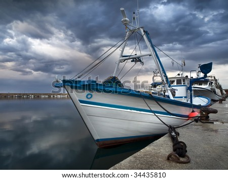 Fishing boat docked at the port, with a stormy sky - stock photo