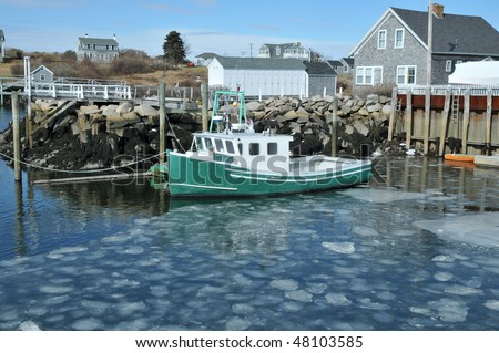 Fishing boat docked in an ice filled harbor at Biddeford Pool, Maine - stock photo