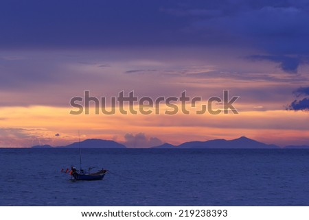 Fishing boat floating on the sea at sunset - stock photo