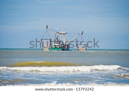 Fishing boat followed by seagulls. - stock photo