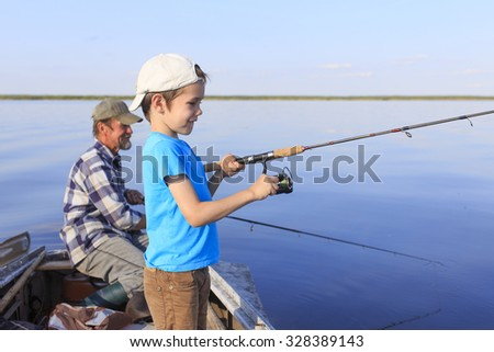 Fishing boat. Grandfather and grandson fishing together on a spinning sitting in a boat on a river - stock photo