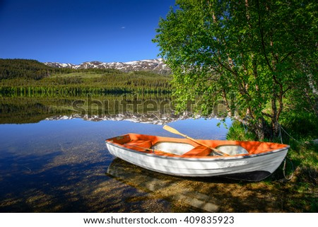 Fishing boat in blue lake in Norway nature - stock photo