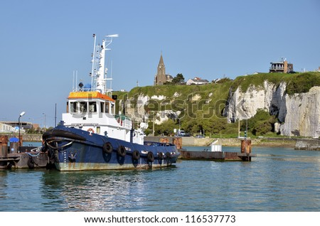 Fishing boat in the port of dieppe and the church Notre Dame in the background on the cliffs. Dieppe is a commune in the Seine-Maritime department in the Haute-Normandie region in northwestern France - stock photo