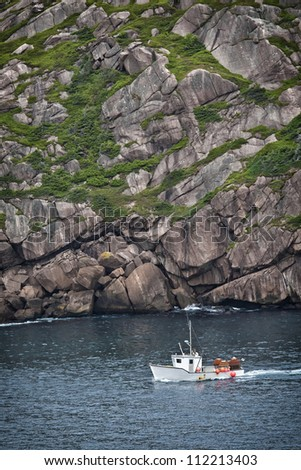 Fishing boat laded with crab traps sailing into St. John's Harbour past Signal Hill, Newfoundland. - stock photo