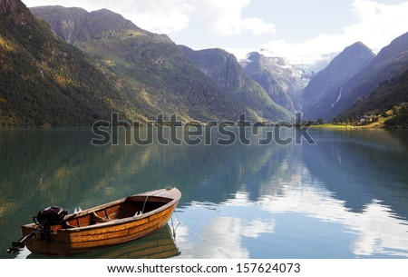 Fishing boat on a still lake in Norway and high mountains in background. - stock photo