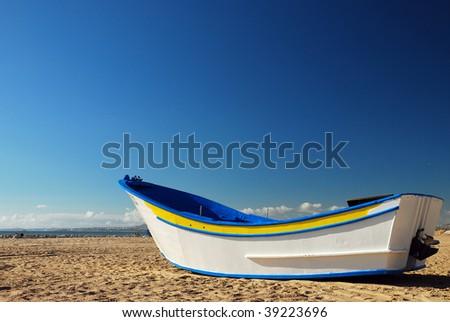 Fishing Boat on an empty beach in Costa da Caparica, Portugal - stock photo