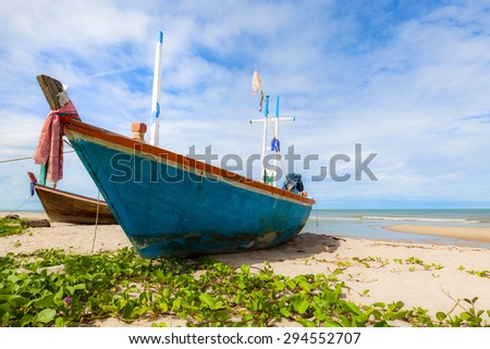 Fishing boat on sand beach and blue sky - stock photo