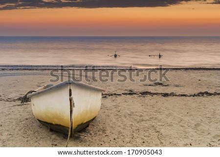 Fishing boat on sandy beach at dawn  - stock photo