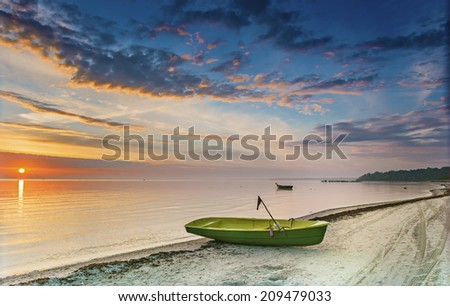 Fishing boat on sandy beach at dawn, Baltic Sea - stock photo