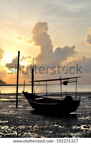 Fishing boat on the beach when sun rising up - stock photo