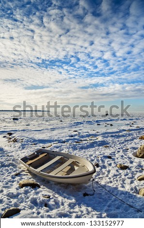 Fishing boat on the sea shore sunny winter afternoon - stock photo