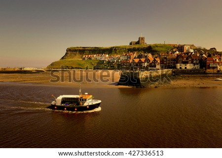 Fishing boat returns to harbour sailing up River Esk, Whitby, North Yorkshire. Warm filter added. - stock photo