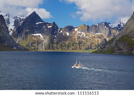 Fishing boat surrounded by seagulls making its way across Reinefjorden on Lofoten islands in Norway - stock photo
