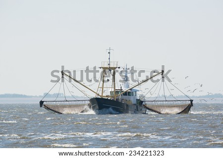 fishing boat with nets on Dutch wadden sea - stock photo