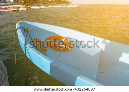 Fishing boat with round lifebuoy moored at caribbean sea  - stock photo