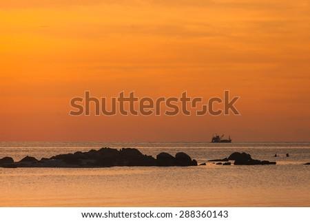 Fishing boat with sunset scene - stock photo