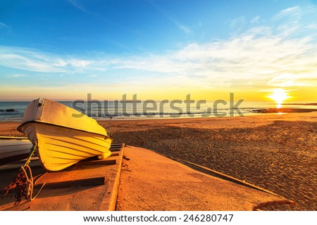 Fishing boats against sunset on the beach in Portugal - stock photo