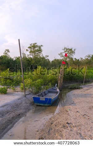 Fishing boats and fishing nets on a tropical beach with mangrove in the background.  - stock photo