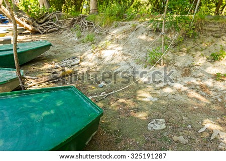 Fishing boats are tied with rope, marooned to the river shore. - stock photo