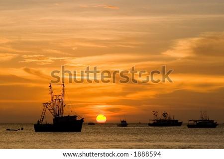 Fishing boats at sunset - stock photo