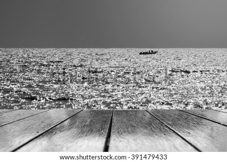 Fishing boats floating in the sea with the wooden floor.black and white process. - stock photo