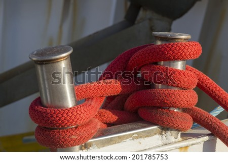 fishing boats in harbor - bollard with red rope - stock photo