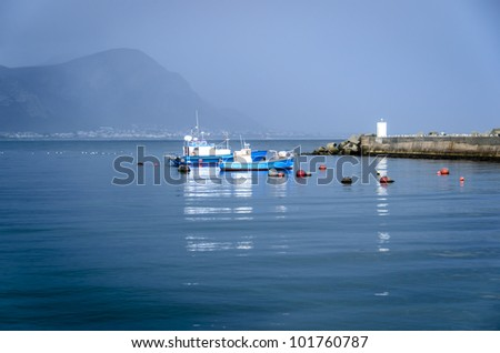 Fishing Boats moored in the Hermanus harbour late afternoon - stock photo