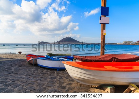 Fishing boats on beautiful El Medano beach at sunrise time, Tenerife, Canary Islands, Spain - stock photo