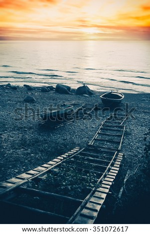 Fishing boats on the beach with stones and wooden ladder at sunset. Baltic Sea - stock photo