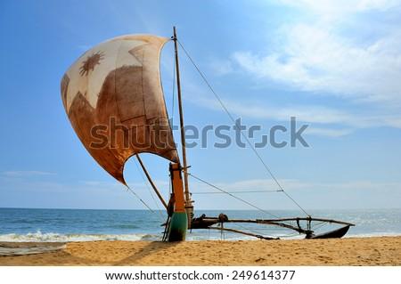 Fishing boats resting on empty beach in Sri Lanka - stock photo