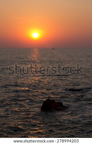 fishing boats return to shore at sunset - stock photo