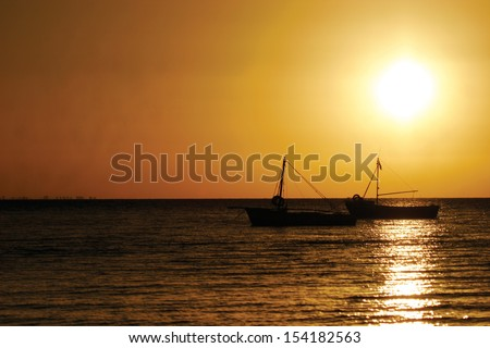 Fishing boats silhouetted against the setting sun in Maputo Bay, Mozambique, Africa. - stock photo