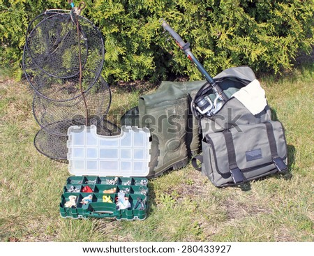 Fishing equipment on grass - stock photo