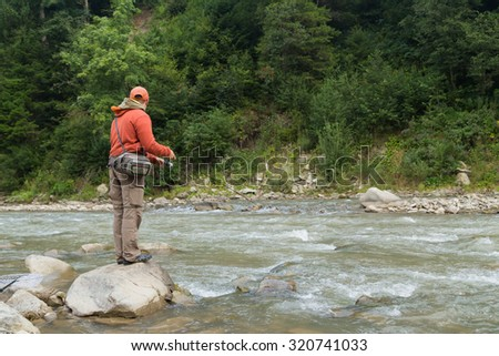 Fishing. Fishing in the highlands. Fisherman on the shore of a mountain, fast river. Trout fishing on the river. Active holiday in the mountains. - stock photo