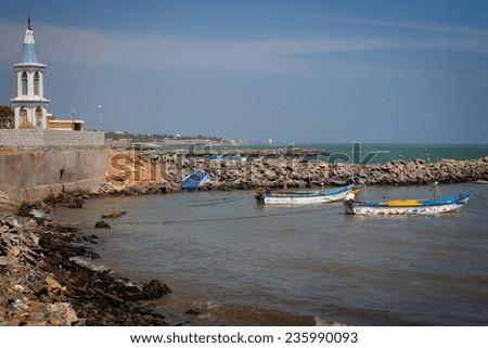 Fishing harbor with large church in background, Laccadive Sea, KanyaKumari, Tamil Nadu, India  - stock photo