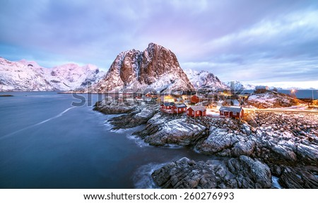 Fishing hut (rorbu) in the Hamnoy and Lilandstinden mountain peak at sunset - Reine, Lofoten islands, Norway - stock photo