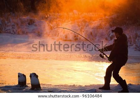 Fishing in the winter on not frozen reservoir - stock photo