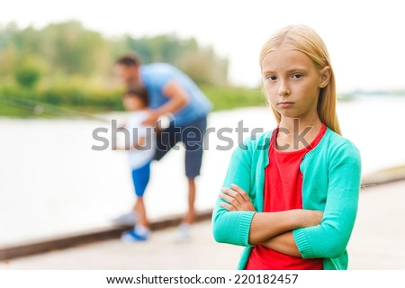 Fishing is too boring for me! Depressed little girl keeping arms crossed and looking at camera while man with little boy fishing in the background  - stock photo
