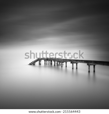 Fishing jetty in black and white . Image has grain texture - noise seen at 100 percent of its size. - stock photo