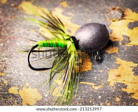 fishing lure on the old shabby table - stock photo