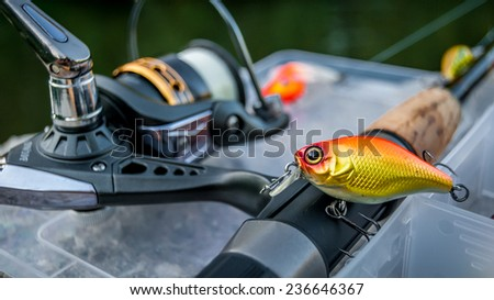 Fishing lure supported on a fishing rod equipped with a reel - stock photo