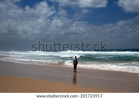 Fishing man on the beach on Gold Coast Australia - stock photo