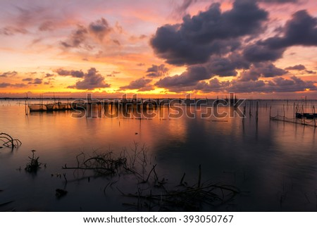 fishing moored at sea. Clouds and light evening twilight and sunset. - stock photo