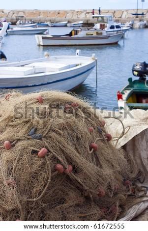 Fishing net and some wooden fishing boats in harbor of Fazana in Croatia - stock photo