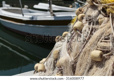 Fishing net and wooden boat in background - stock photo
