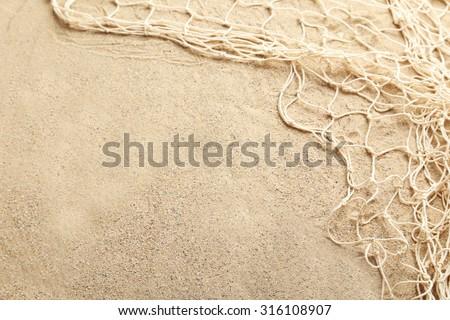 Fishing net on a beach sand - stock photo