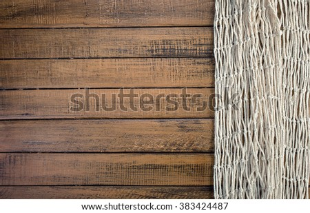 Fishing net on old wooden board background with copy space - stock photo